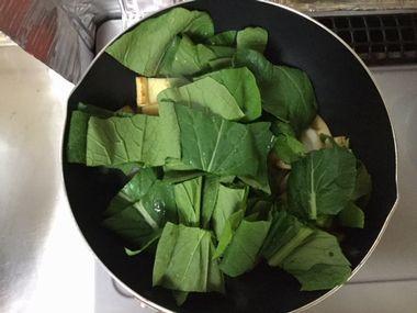 小松菜の葉の部分を加えて炒めます。