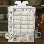 手作りしたお薬カレンダーを食器棚に立てかけてみています。