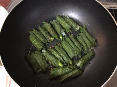 油を敷いたフライパンに大根とししとうを巻いた紫蘇をのせて焼いています。