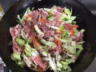 焼きそばを作っています。中華鍋に、野菜とお肉を入れて炒めています。