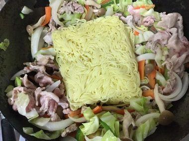 焼きそばを作っています。野菜とお肉を軽く炒め、めんを投入しました。