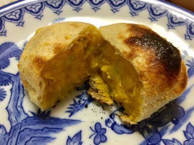 焼けたかぼちゃとチーズの油あげ包みを包丁で切った様子です。