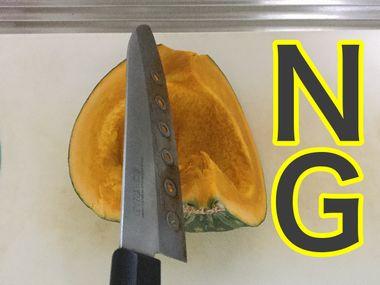 かぼちゃの皮目を下にして、まな板の上に置いた状態で包丁を当てています。