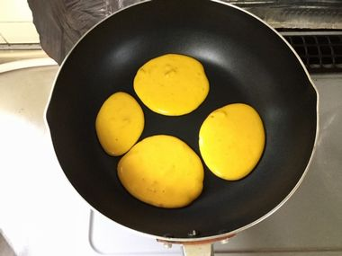 弱火で熱したフライパンに、かぼちゃのパンケーキの生地を4枚分流し入れた様子です。
