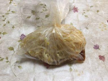 茹でたもやしをビニール袋に入れて調味料と合わせています。
