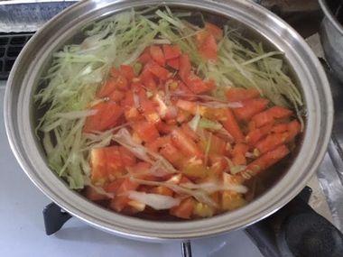 キャベツとトマトのスープを作っています。