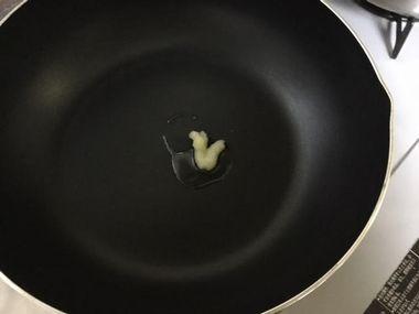 フライパンに油とにんにくが入っています。