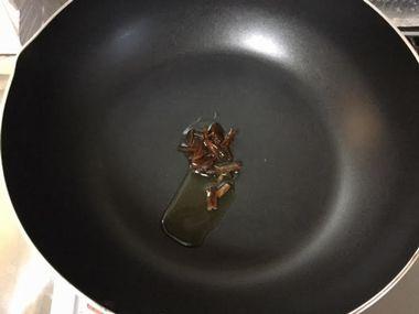 フライパンにごま油と千切りにんにくが入っています。