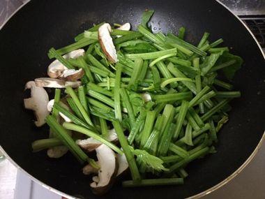 ホウレン草と椎茸をフライパンで炒めています。