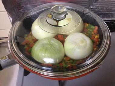 玉ねぎをフライパンでふたをして煮ようとしています。