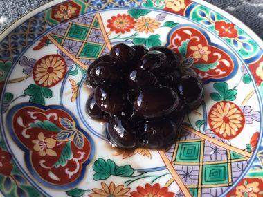 らっこが煮た黒豆です。赤緑金白色鮮やかな中華風の小皿によそっています。