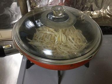 フライパンでもやしを蒸し焼きにしています。