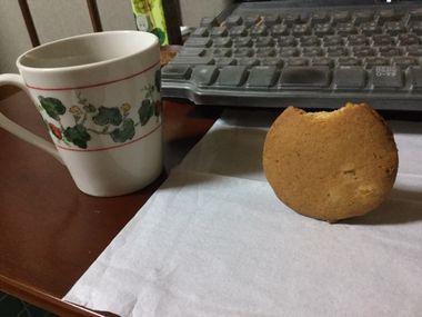 パソコンの前で自立して立っているかじりかけのクッキーです。