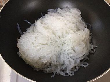 フライパンでしらたきを炒めています。