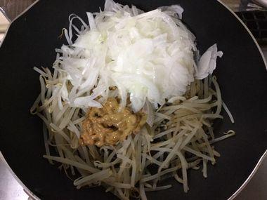 フライパンの中に、もやしと納豆と新玉ねぎが入っています。