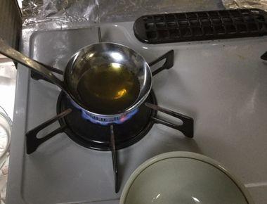 お玉に注いだごま油を熱しています。