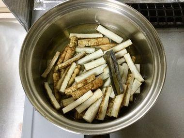 小鍋に、水と昆布とゴボウが入っています。