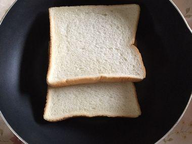 フライパンに食パンを2枚並べようとした様子です。