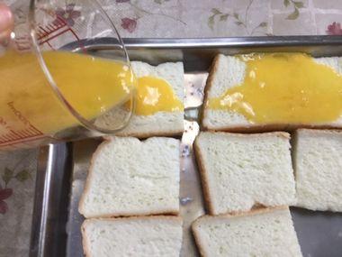 食パンに卵液をかけています。