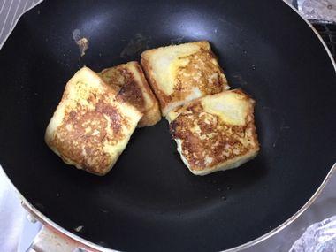 フレンチトーストの焼き色を確認しています。