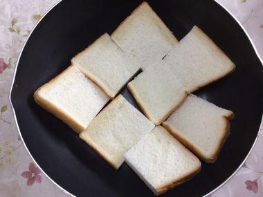 フライパンに4つ切り食パンを並べた様子です。