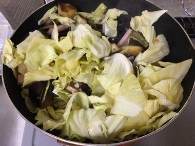 ナスとキャベツとハムを炒めています。