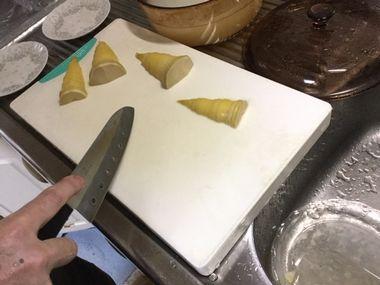 茹でたタケノコを刻んでいます。