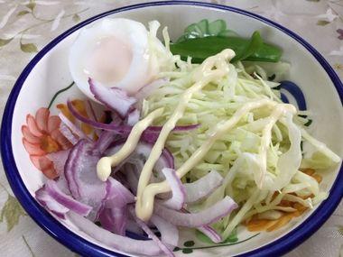 マヨネーズをかけた紫玉ねぎとキャベツとゆで卵のサラダです。