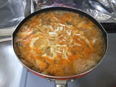 雑炊にチーズを振りかけています。