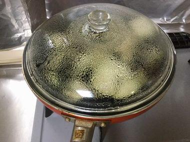 フライパンで蒸し焼きにしているナスです。ふたに水滴が付いています。