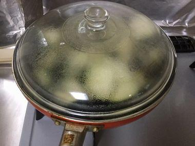 フライパンにふたをしてナスを蒸し焼きにしています。