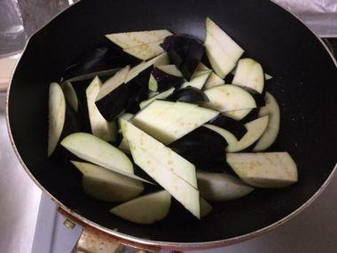 刻んだナスをフライパンで炒めています。