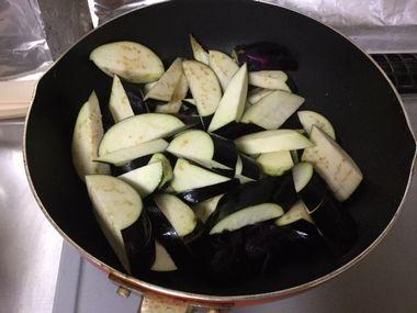 フライパンでナスを炒めています。