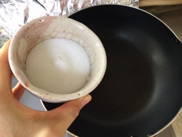 フライパンにグラニュー糖を入れるところです。