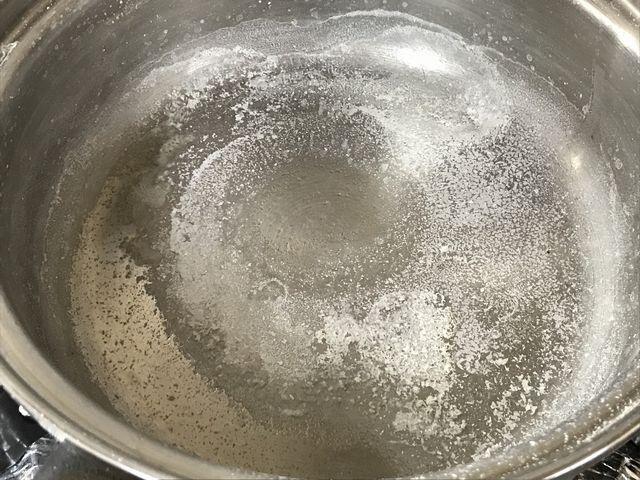 鍋に残った塩を取り出そうとしています。