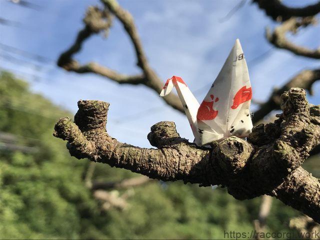 松の木の枝にとまった折り鶴